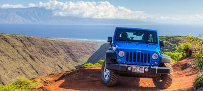 blue jeep on top of lanai with maui in the background