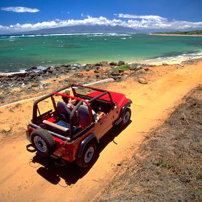 red jeep driving along gorgeous lanai coastline